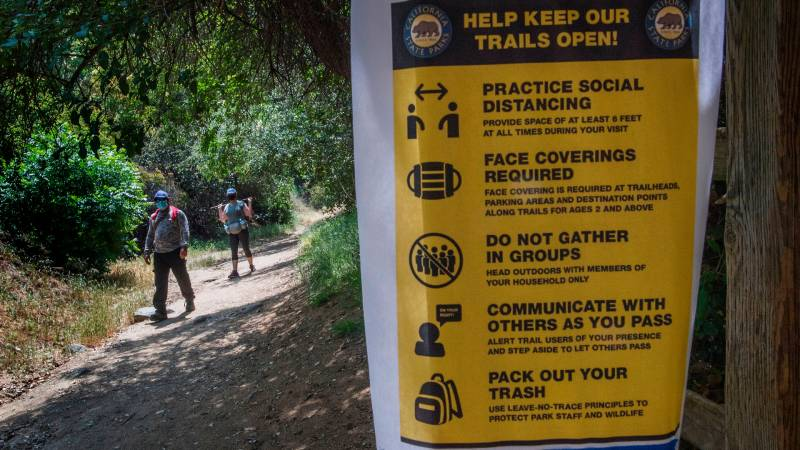 Hikers walk through trail with masks on while signs of social distancing are put up