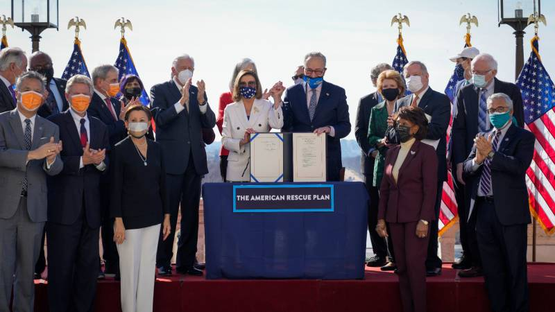 Nancy Pelosi and Chuck Schumer stand behind a podium holding the covid relief bill, surrounded by members of congress