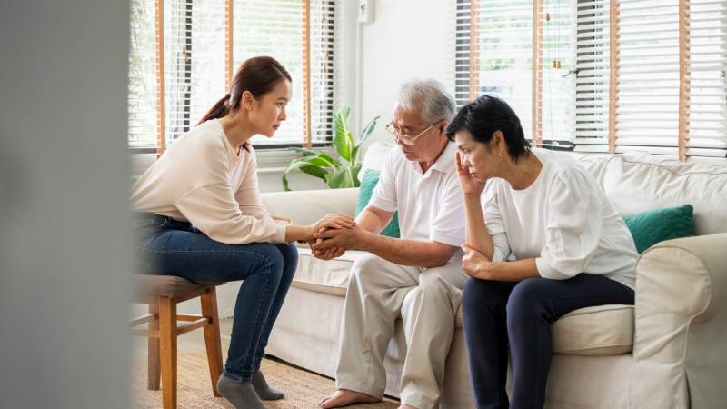 Three Asian people converse seriously (stock image)