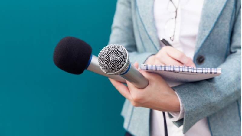 Woman holds two mics and a notebook