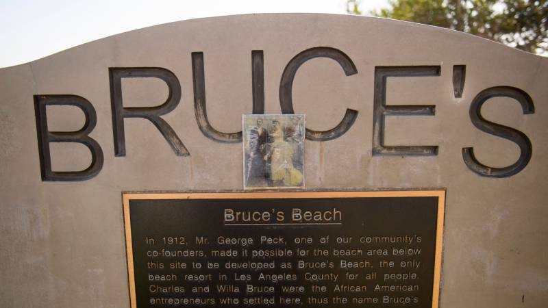 A photo of Charles and Willa Bruce stands above a plaque that tells the history of Bruce's Beach