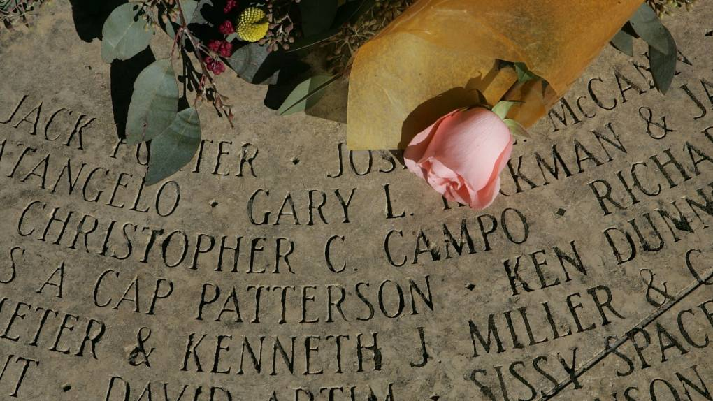 """A rose is seen placed on the """"Circle of Friends,"""" a ring of names engraved in stone to honor those who have been affected by AIDS at the AIDS Memorial Grove"""