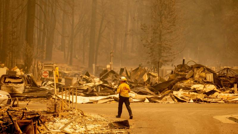 A firefighter surveys a destroyed downtown during the Dixie fire in Greenville, California on Aug. 5, 2021.