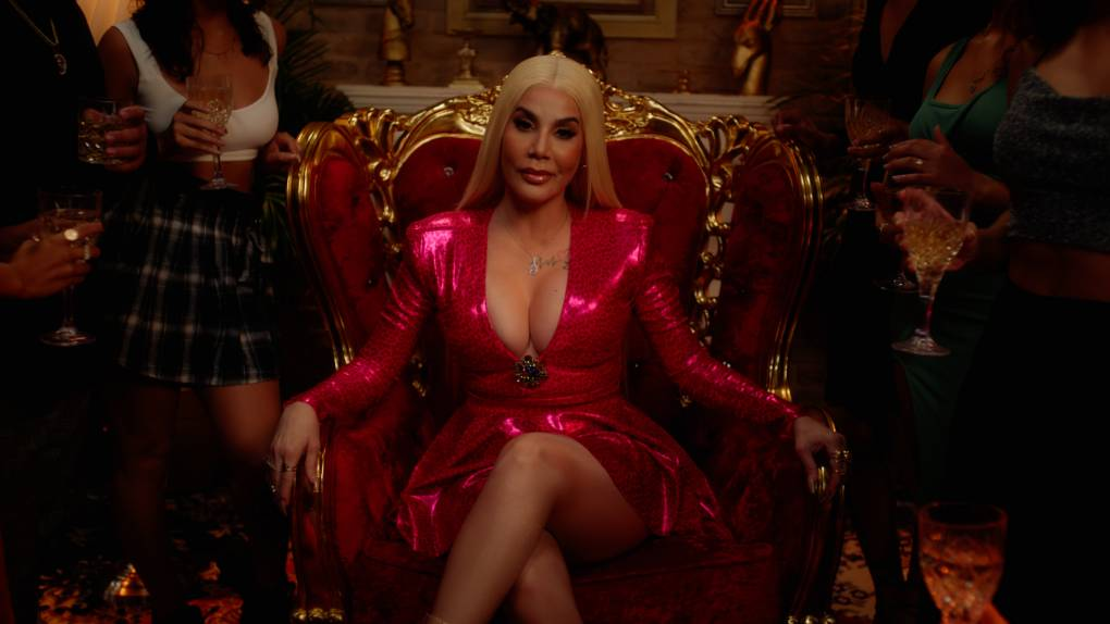 Woman with straight blonde hair and sparkly pink dress sits on a throne