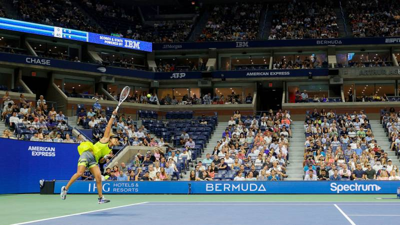 The tennis ball from Naomi Osaka's serve is in midair as she is captured post-serve, still in the air, in front of onlookers in the stands surrounding the court.