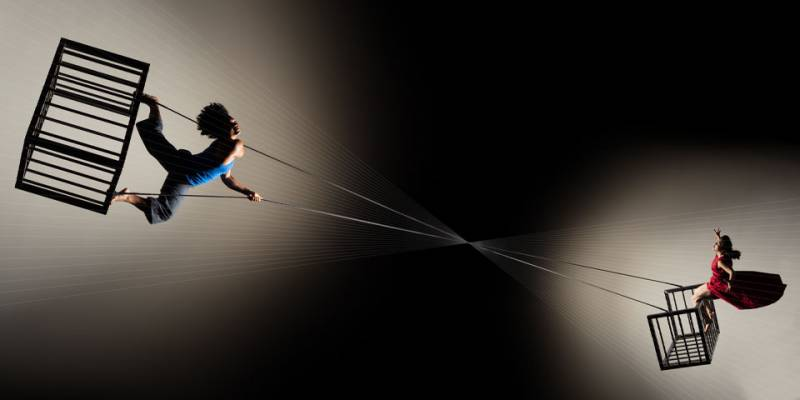 Two aerial dancers pulling strings connecting their cages.