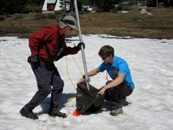 Surveyor Frank Gehrke takes on last poke at the season's shrinking snow pack. Photo by Craig Miller.