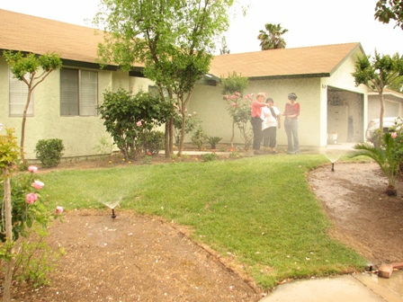 KQED's Sasha Khokha braves sprinkler spray to record Fresno's city water conservation team at work.