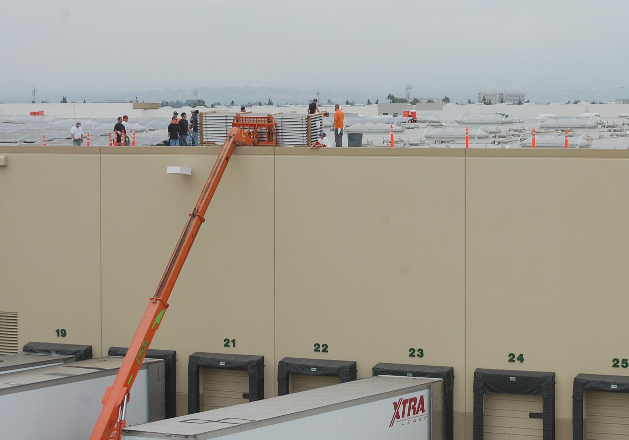 Hoisting panels onto warehouse roof. Photos: Ilsa Setziol