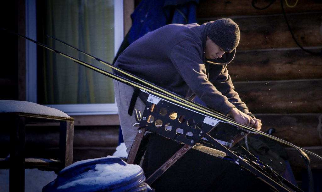 Joe Bifelt waxing his sled before the community New Years dogsled race.