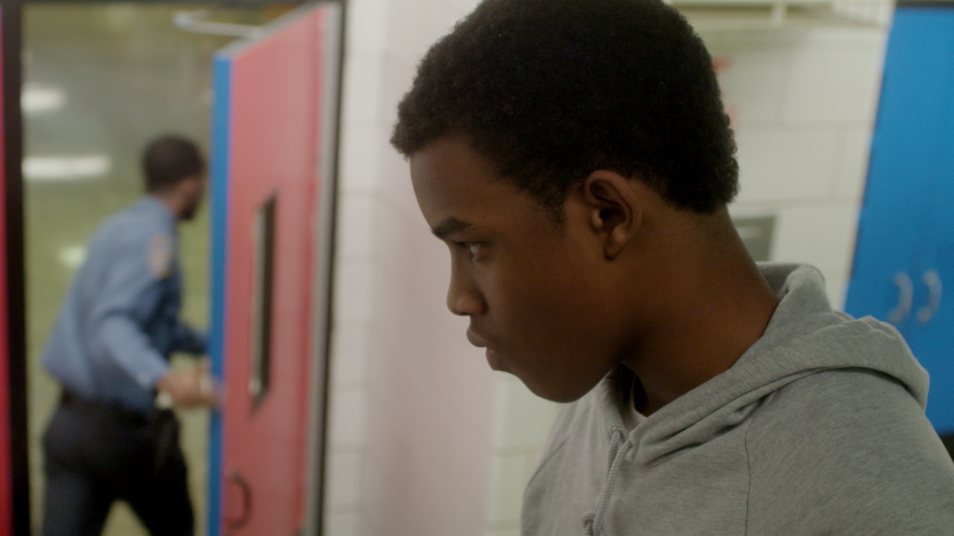 Joseph waits on the stairs as Mike (played Duane Cooper) chases after another student.
